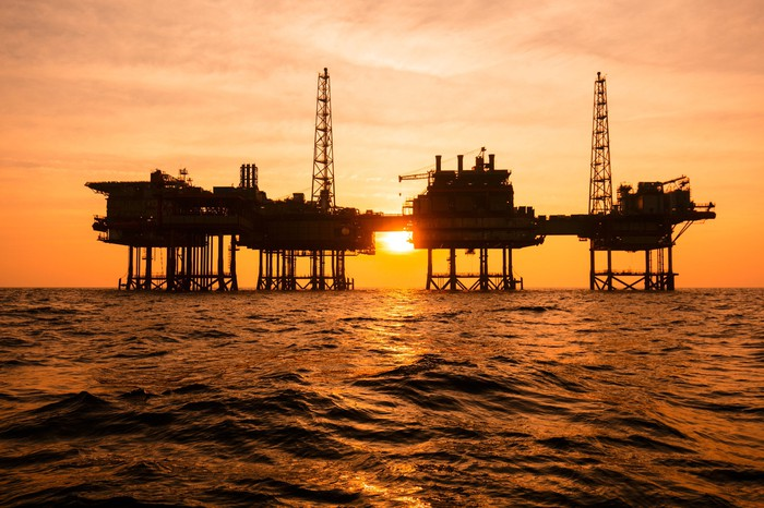 An offshore oil rig in silhouette against a sunset in open water.