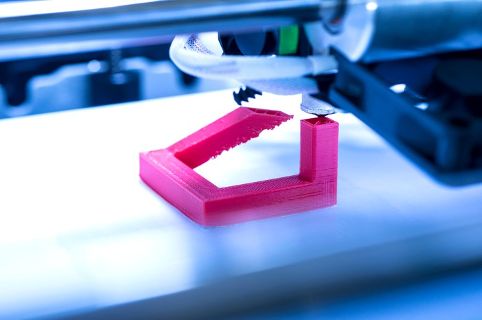 Close-up of 3D printer printing a fuschia-colored plastic object.