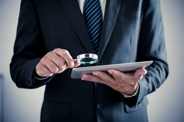 A businessman holding a magnifying glass up to a tablet.