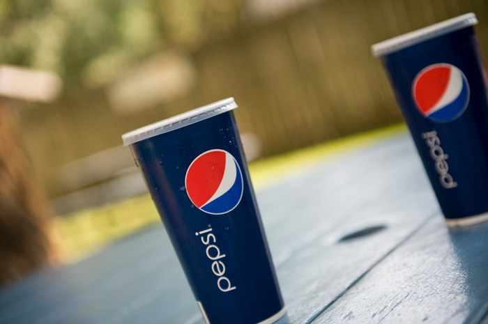 Two cups of Pepsi on a wood picnic table in a fenced-in backyard.