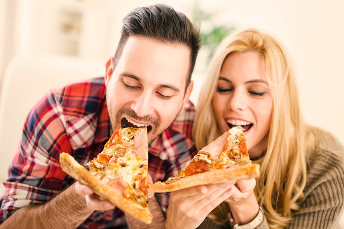 A man and a woman each taking a bite of a slice of pizza.