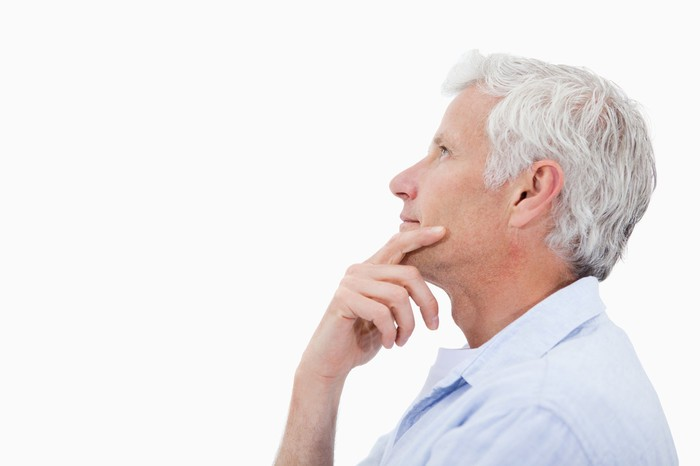 A gray-haired man in profile holds his hand to his chin in thought.