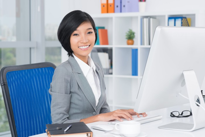 A woman typing on a desktop computer and smiling