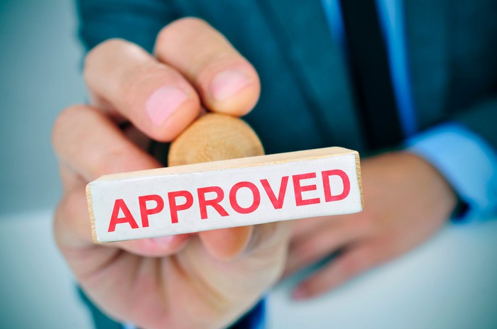 A business person holds a rubber stamp reading approved.