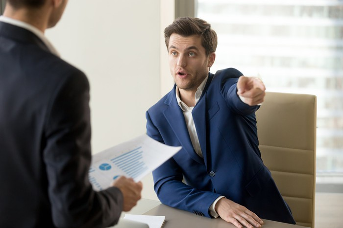 Man in suit pointing toward the door while meeting with another man holding a document