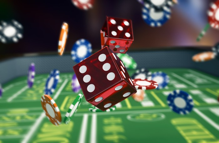 Dice and chips rolling around on a craps table.