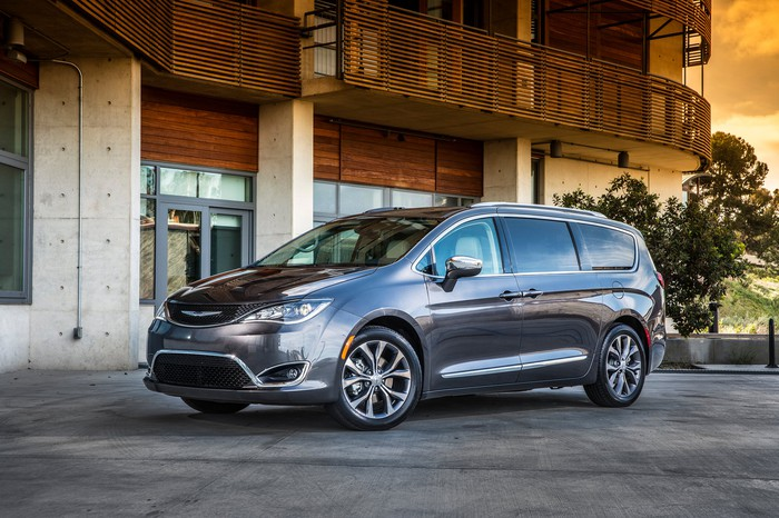 A dark silver Chrysler Pacifica minivan parked in front of a stylish wood-and-concrete building.