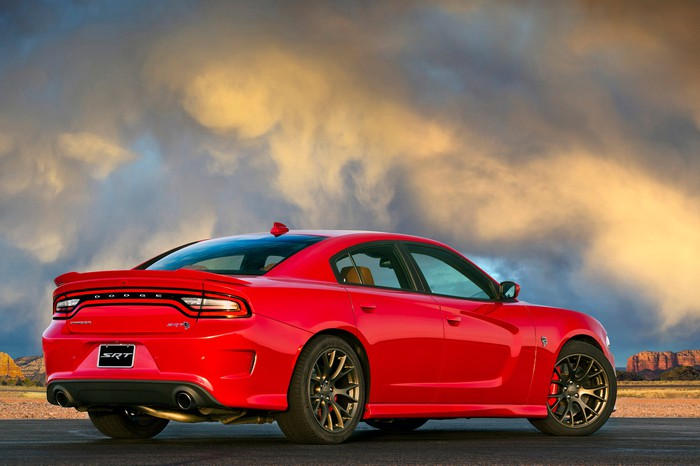 A red 2017 Dodge Charger SRT Hellcat, a full-size sedan, parked on a desert road.