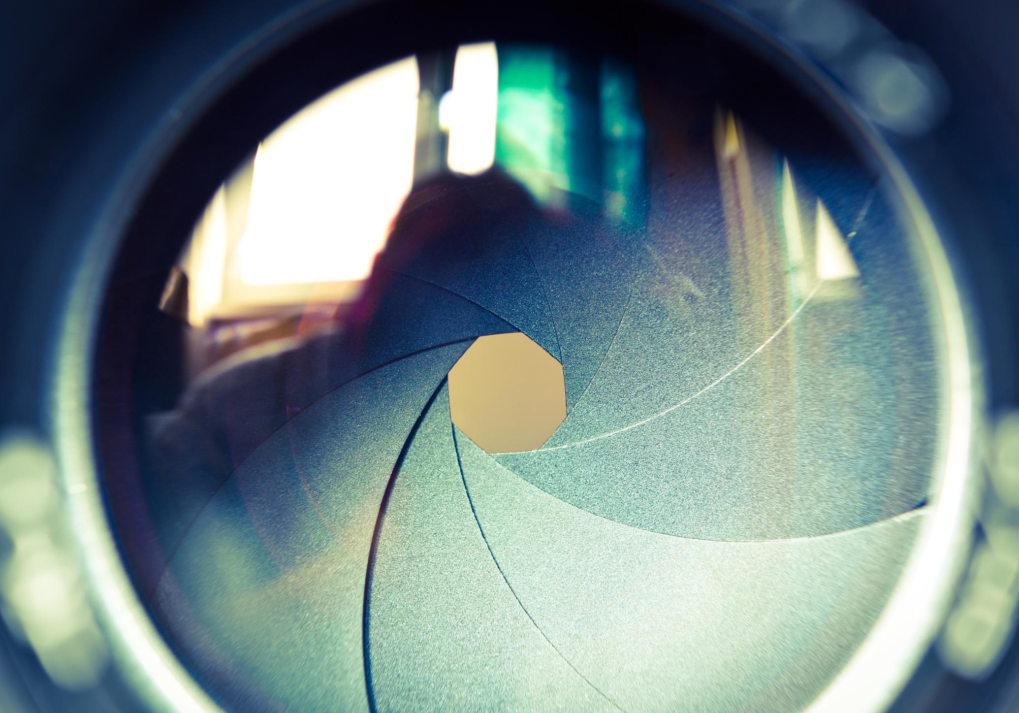 Close-up of a camera lens with narrow aperture.