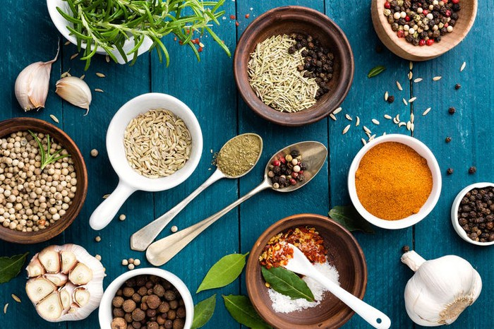 Culinary background with various colorful spices on a blue wooden table.
