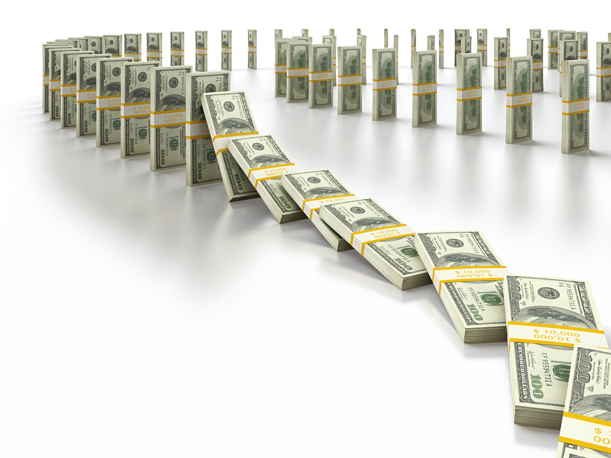 Stacks of money falling like dominoes