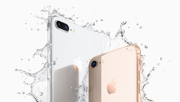 Apple's iPhone 8 Plus in silver on the left, and its iPhone 8 in gold on the right, both being splashed by water.