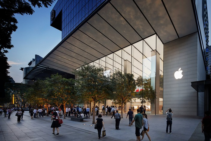 Apple Store with trees and pedestrians in front.