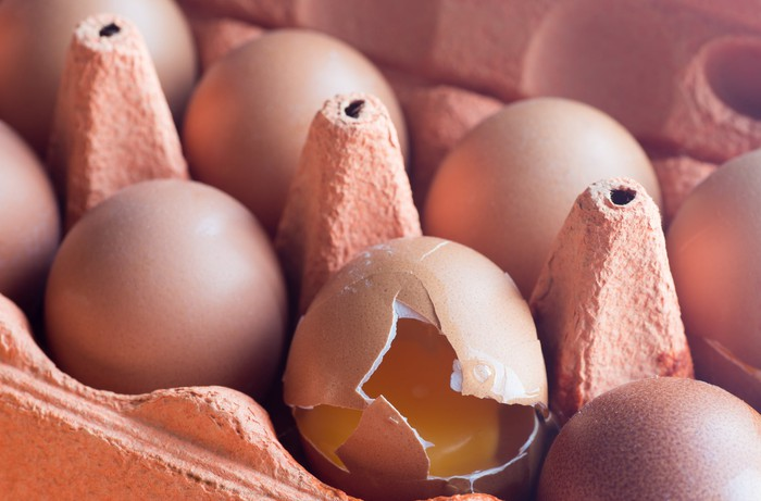 Close-up of eggs in a carton; one of them is cracked and the yolk is showing.