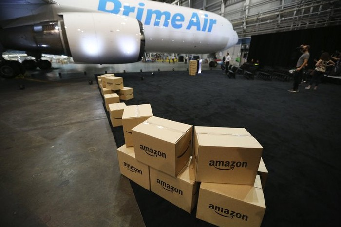 Amazon boxes in an airplane hanger with a Prime Air aircraft.