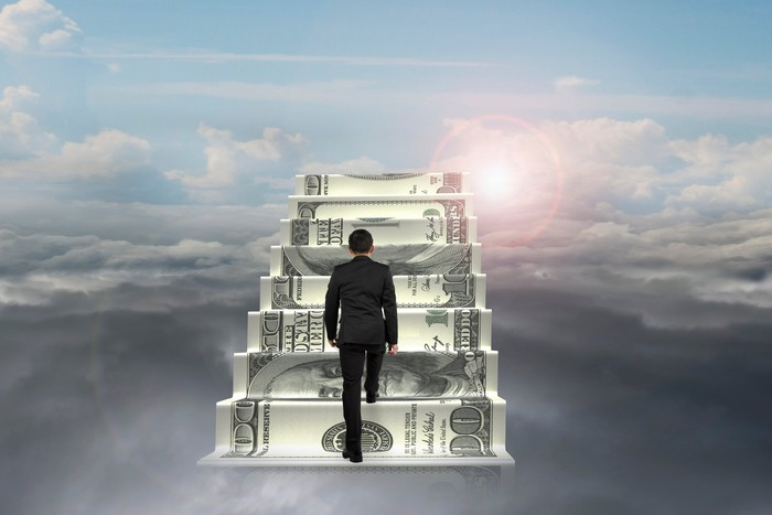Man in suit walking up steps made of hundred-dollar bills above the clouds