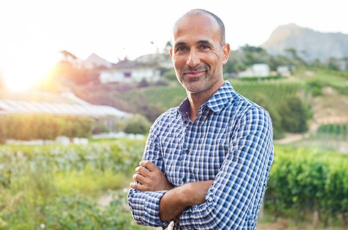 40-something man standing in a vineyard.