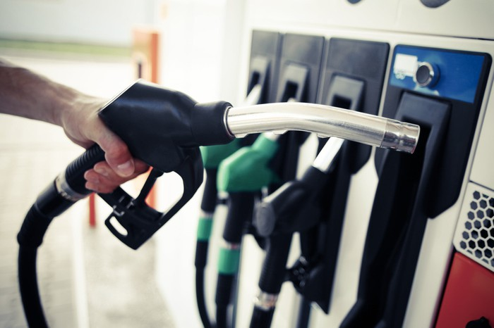 A hand holding a gas nozzle in front of a filling station pump