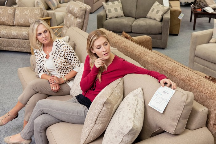 Two women sit on a couch in a furniture store looking at the price tag