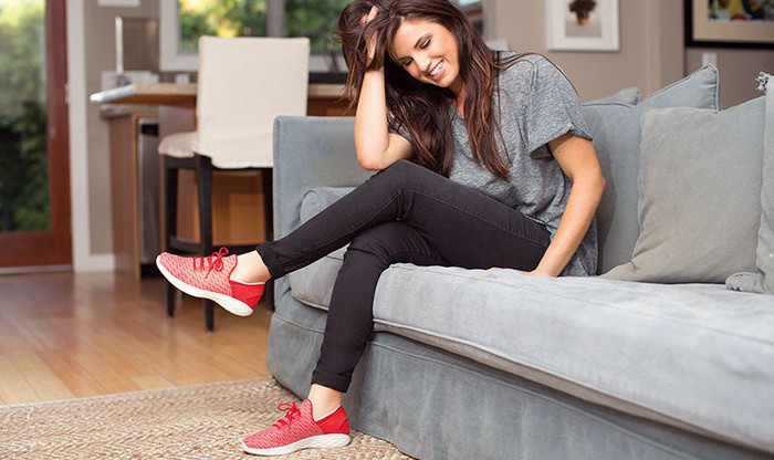 Woman sitting comfortably on a couch with red Skechers on her feet.