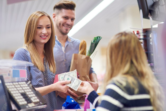 A woman and man checking out at a grocery store and paying in cash.