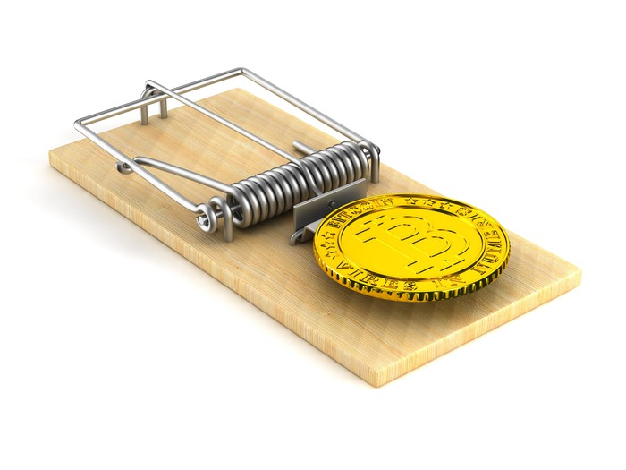 A gold physical bitcoin placed at the end of a mouse trap.