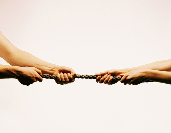 Two pairs of arms and hands playing tug-of-war with a rope