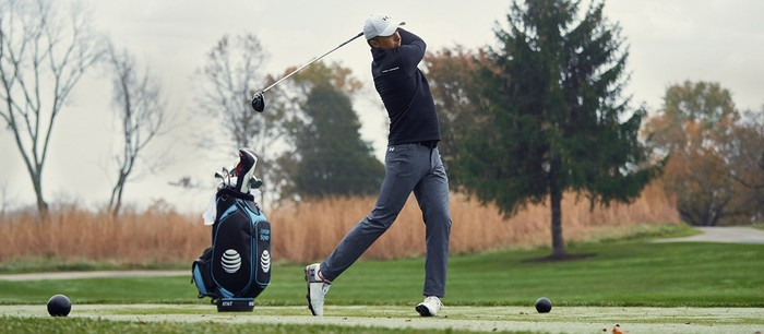 Golfer Jordan Spieth teeing off while wearing Under Armour gear
