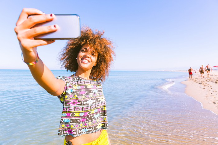 A young woman takes a selfie at the beach.