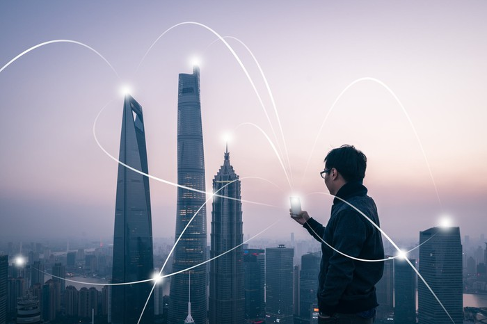 A man standing in front of a Chinese city landscape, connecting to information points throughout the city with his mobile device.