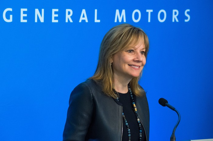 "Mary Barra stands before a blue backdrop with the words ""General Motors"" visible, during a presentation to GM shareholders on June 6, 2017."