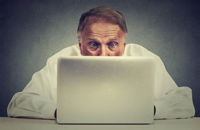 Older man looking at computer screen with a surprised look on his face.