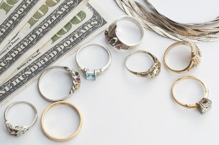 $100 bills, a necklace, and eight rings on a white background.