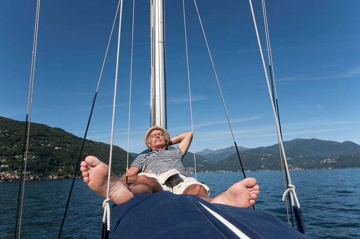 An man napping on a sail boat.