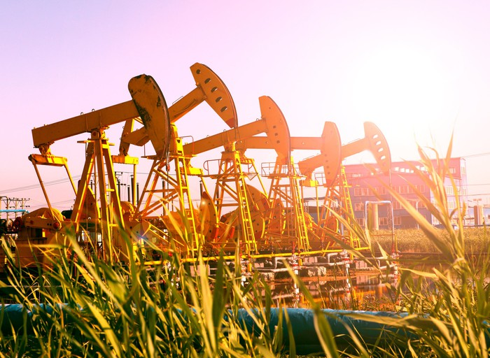 Several pumpjacks in a row with a sunburst shining on them.