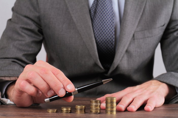 Stack of progressively larger coins on a desk while a business person points in the direction of the coin stacks.