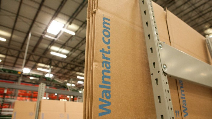 """Flat-packed cardboard boxes with """"Walmart.com"""" printed on them sitting in a warehouse."""