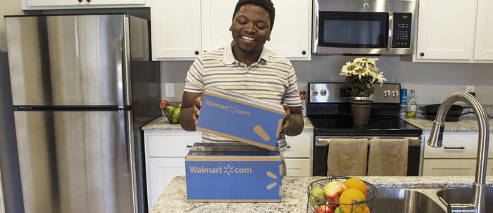 A young man holds a Wal-Mart box.
