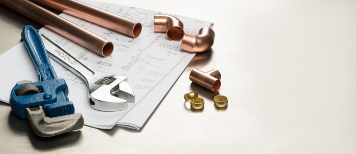 Wrenches, copper pipes, and pipe fittings atop a set of plans.