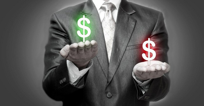 A man in a suit holds a green and red dollar sign in each hand as if weighing them.
