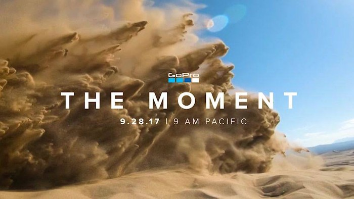 Flying sand kicked up by a motorcycle riding in the desert with a blue sky background and the words The Moment in the foreground with the date and time underneath and a GoPro logo.