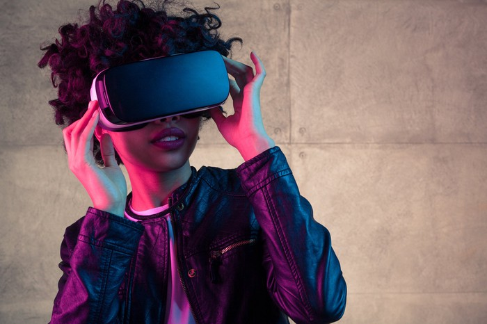 Woman with VR headset on and bright lighting in the background.