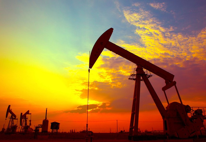 An oil pumping unit with a brightly colored sunset in the background.