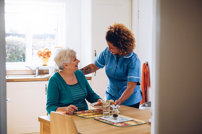 Woman in scrubs helping older woman at the table