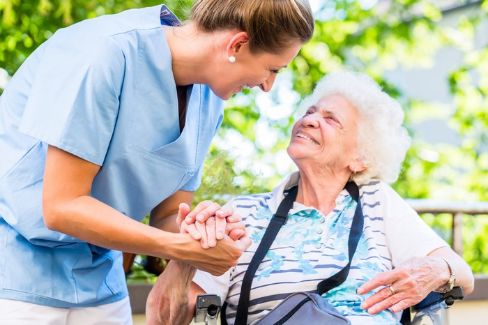 Woman in scrubs leaning down to hold elderly woman's hand