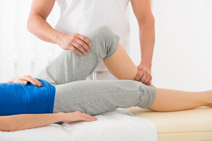 Physical therapist stretching patient's leg