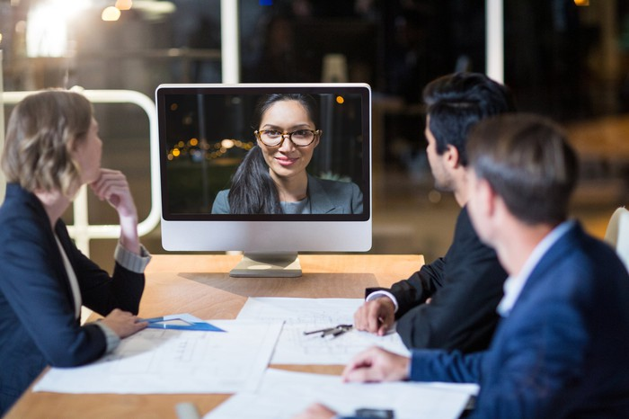 In a teleconference, three people in business attire are gathered around a table, with papers laid out on the table between them, as they look at a person on a monitor.