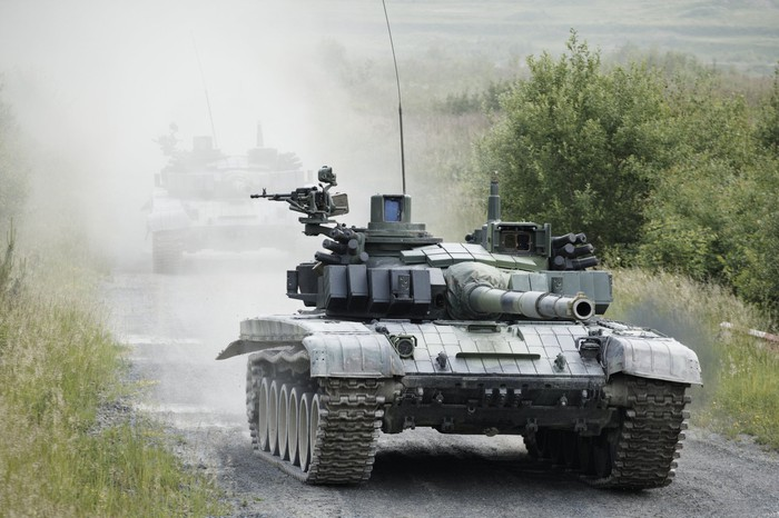 Military tanks on a dusty road.
