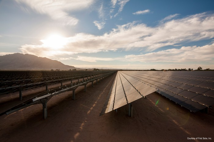 Large, utility scale thin-film solar installation by First Solar in the desert with partly cloudy skies in the background.