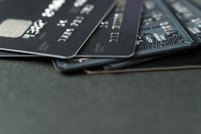 Five credit cards fanned out on a dark table.